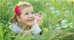 Girl playing with bubbles in grass